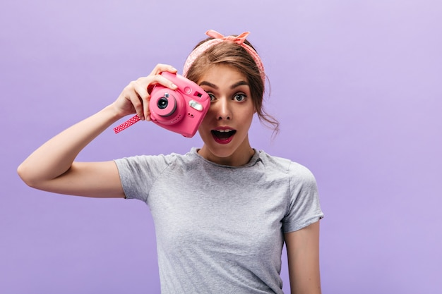 Meisje in grijze outfit houdt roze camera op paarse achtergrond. jonge grappige vrouw met zomer hoofdband in grijs t-shirt poseren.