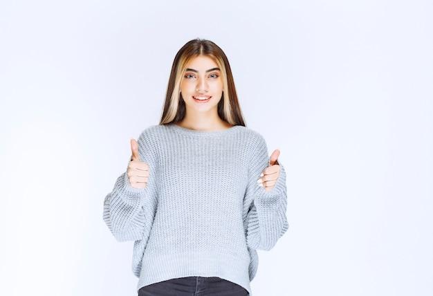 Meisje in grijze sweatshirt duim opdagen.