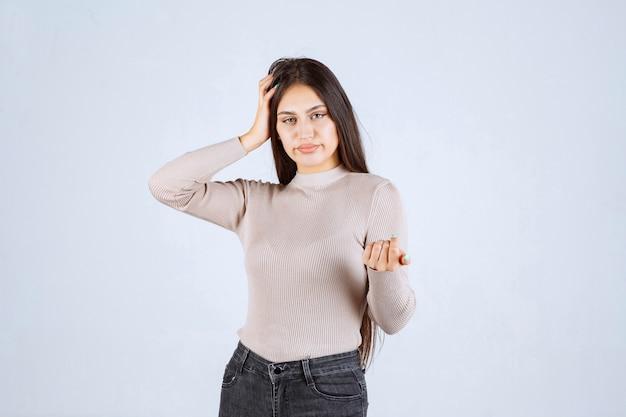 Meisje in grijze trui met haar gezicht en hoofd. Gratis Foto