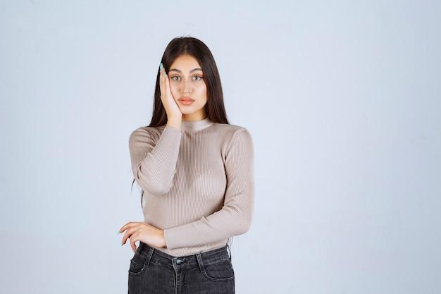 Meisje in grijze trui met haar gezicht en hoofd.