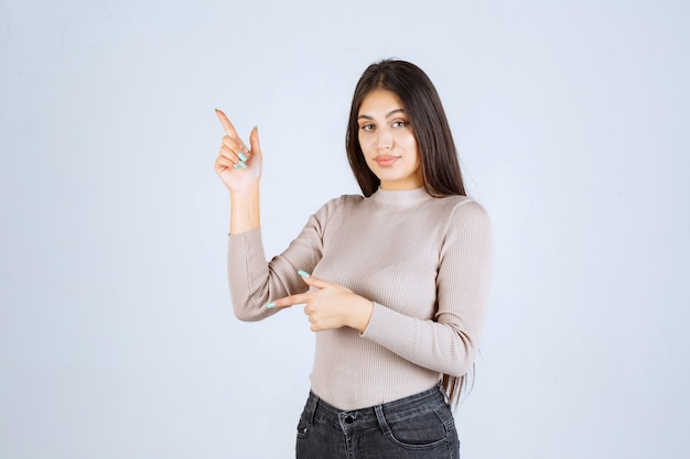Meisje in grijze trui met links iets.