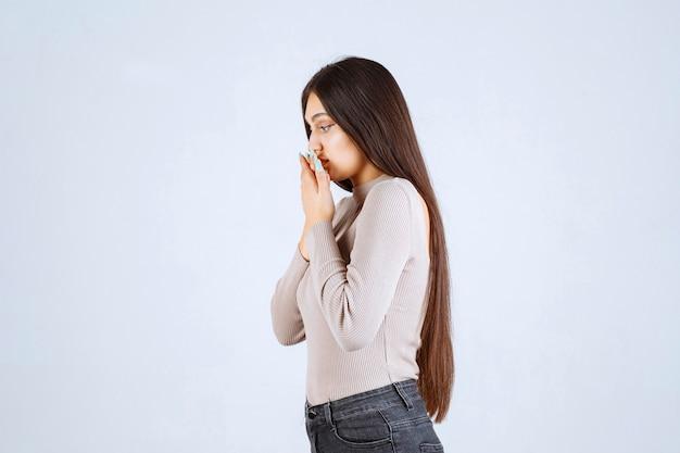 Meisje in grijze trui ruikt vies en bedekt neus.