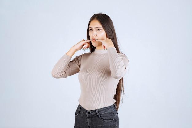 Meisje in grijze trui vingers aan haar mond brengen en fluiten.