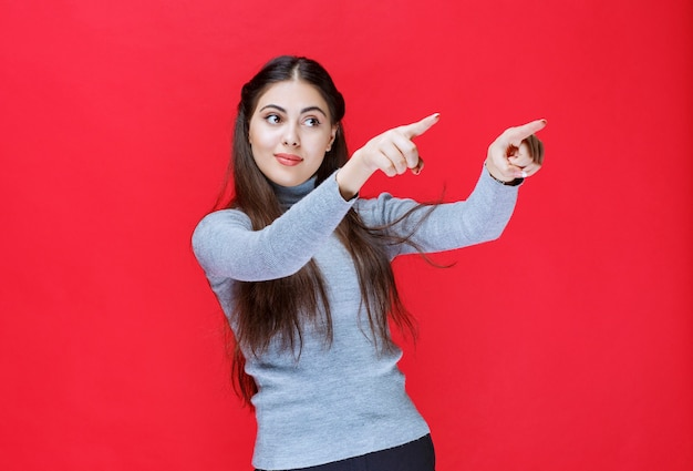 Meisje in grijze trui wijzend op iets aan de rechterkant.