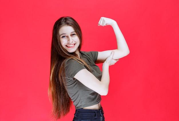 Meisje in groen shirt dat haar armspieren demonstreert.