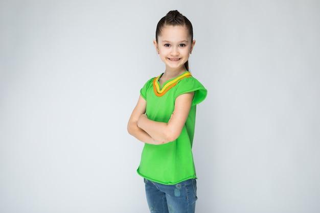Meisje in groen t-shirt en spijkerbroek