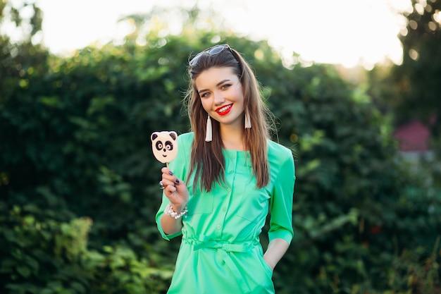 Meisje in groene kleding die snoeppanda op stok toont.