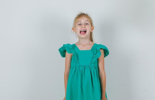Meisje in groene kleding die tong toont en vrolijk kijkt