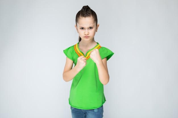 Meisje in groene t-shirt en jeans op grijs.