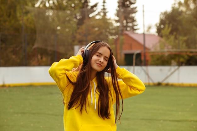 Meisje in grote draadloze koptelefoon buiten op straat, luisterend naar muziek, glimlachend