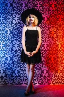 Meisje in heks hoed tegen patroon achtergrond