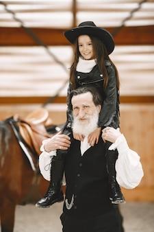 Meisje in helm leren paardrijden. instructeur leert klein meisje.