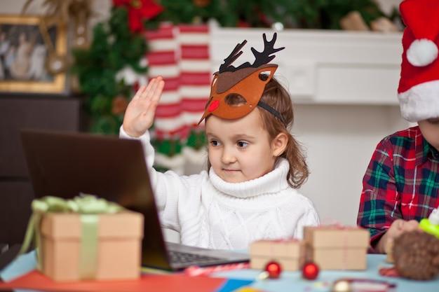 Meisje in herten masker met een geschenkdoos en met behulp van een digitale tablet laptop notebook