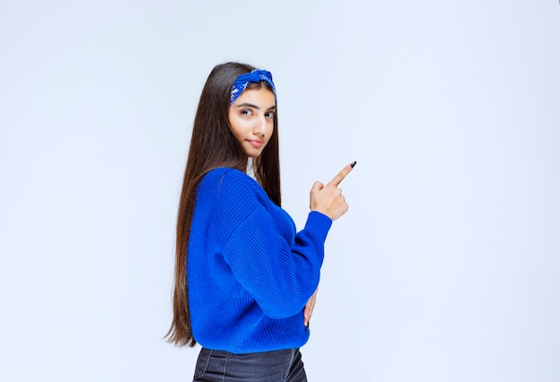Meisje in het blauwe shirt wijzend naar iets aan de rechterkant.
