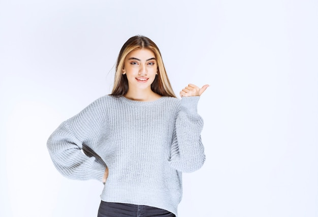 Meisje in het grijze shirt wijzend naar ergens of iemand.