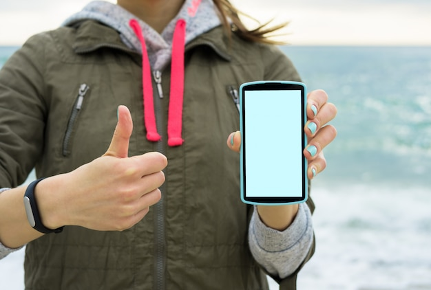 Meisje in het groene jasje op het strand dat het mobiele telefoonscherm toont