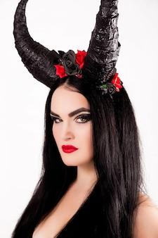 Meisje in het kostuum van een sprookjesachtige held met hoorns op haar hoofd