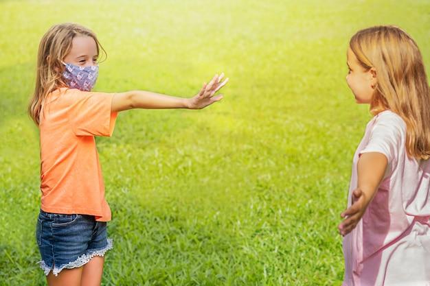 Meisje in het masker toont een halte voor meisje zonder masker. social distancing.
