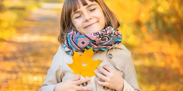 Meisje in het park met herfstbladeren.