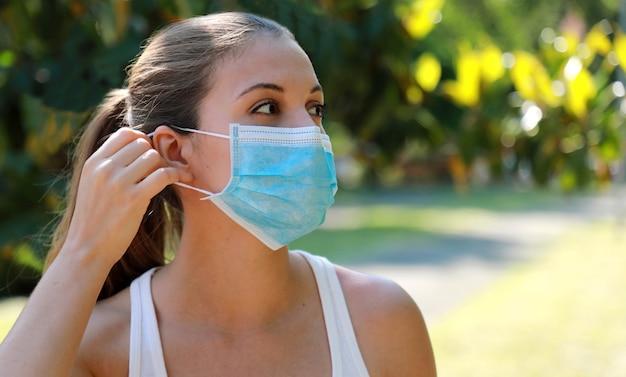 Meisje in het park zet een medisch masker op. jonge sportieve vrouw die chirurgisch masker in stadspark draagt. kopieer ruimte.