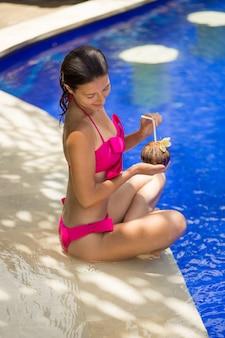 Meisje in het roze zwempak rust op de rand van het zwembad met kokosnoot