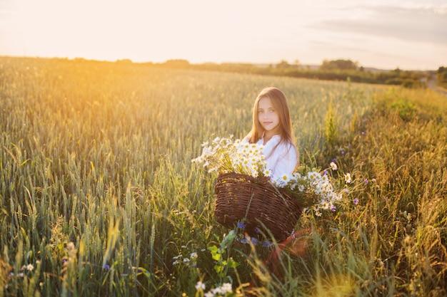 Meisje in het tarweveld met mand met bloemen