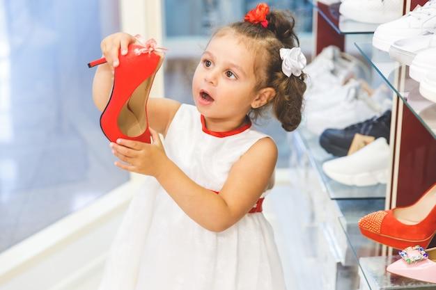 Meisje in het winkelcentrum kiest schoenen