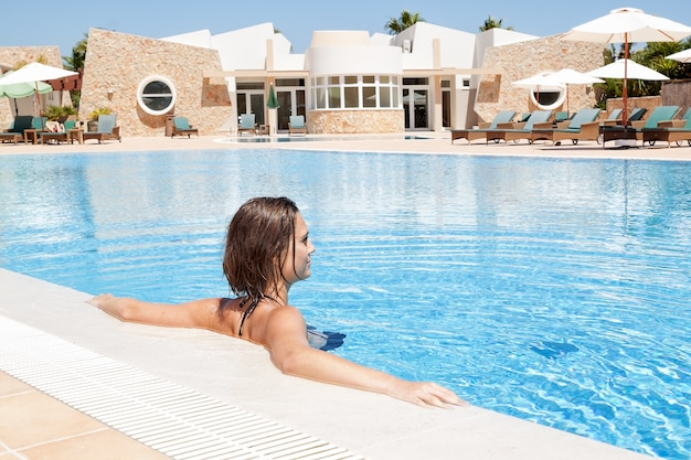 Meisje in het zwembad in het water rust op vakantie.