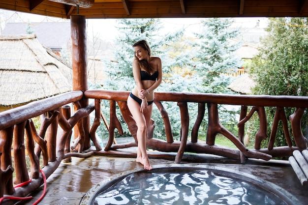 Meisje in het zwembad met warm water op het terras, lichaamsbehandelingen in de spa. ontspan in de open lucht, wellness. huisje met bubbelbad. buitenjacuzzi. jacuzzi met een meisje. mooie figuurvrouw in een zwempak