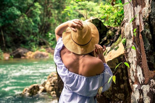 Meisje in hoed aan de rivier