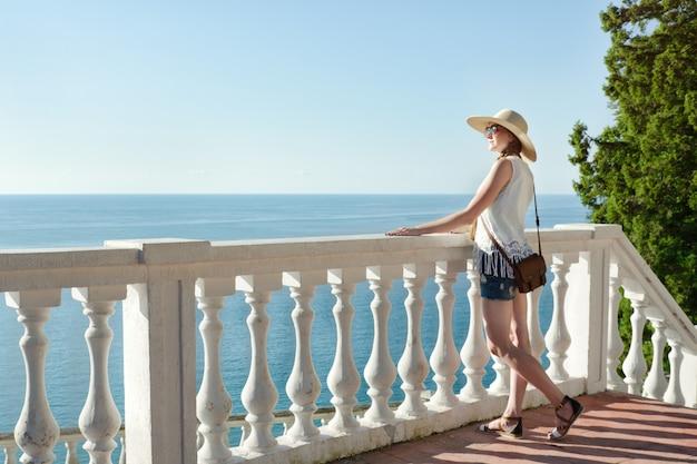 Meisje in hoed die zich op de treden bevindt en het overzees bekijkt. zijaanzicht