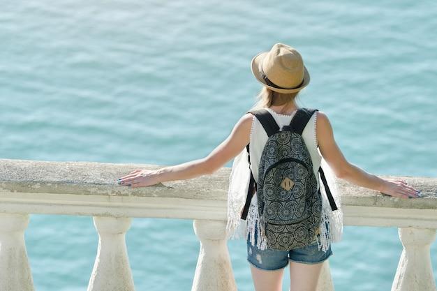 Meisje in hoed die zich op het balkon bevindt en het overzees bekijkt. achteraanzicht