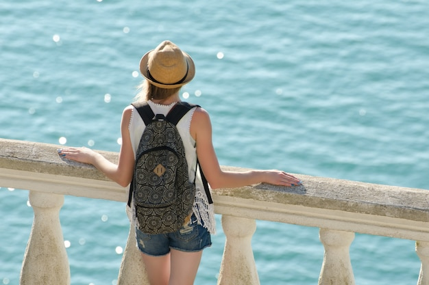 Meisje in hoed die zich op het balkon bevindt en het overzees bekijkt.