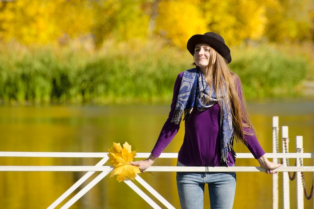 Meisje in hoed die zich op het dok bevindt