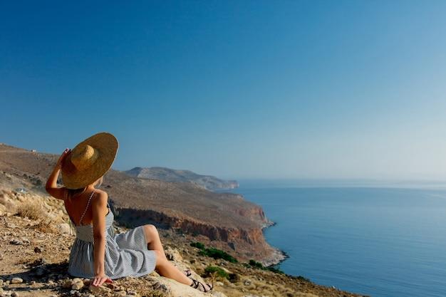 Meisje in hoed en kleding met overzeese kustlijn