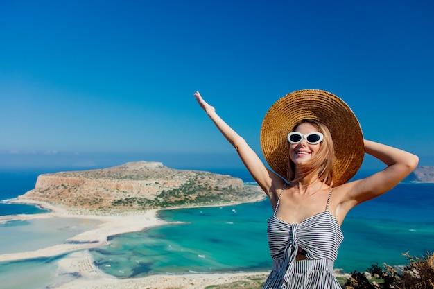Meisje in hoed en kleding met zee kust