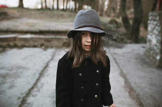 Meisje in hoed en vacht poseren buiten