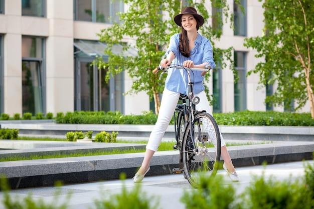 Meisje in hoed fietsen op straat