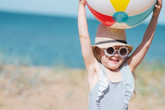 Meisje in hoed het spelen op strand met bal, zonnige de zomerdag. concept vakantie