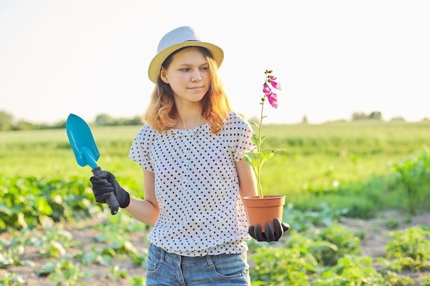 Meisje in hoed met bloeiende potplant en tuin schop