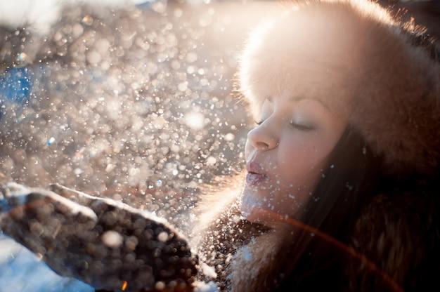 Meisje in hoed met oorkleppen die op de sneeuw blazen.