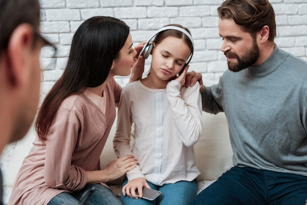 Meisje in hoofdtelefoons die ouders in therapie negeren