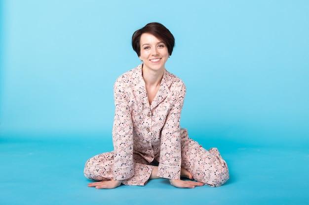 Meisje in huis draagt pyjama met plezier over blauwe muur.