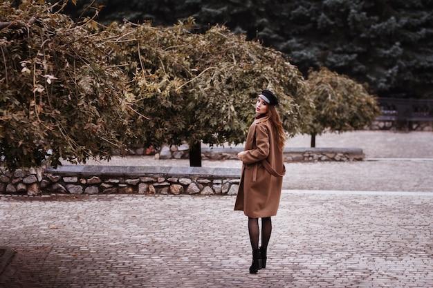 Meisje in jas loopt in het park in de herfst