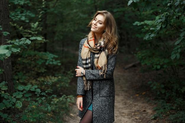 Meisje in jas met een sjaal in het park van struiken.