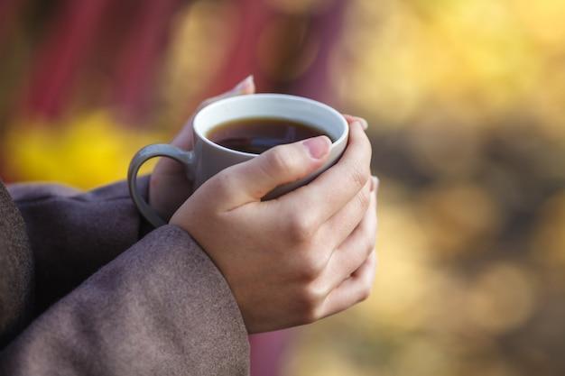 Meisje in jas zittend op de bank, met een kopje koffie of thee, een jong buitenleven, lente of herfst, levensstijl, het concept van de stad, levensstijl