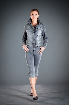 Meisje in jeans collectie kleding op een donkere muur