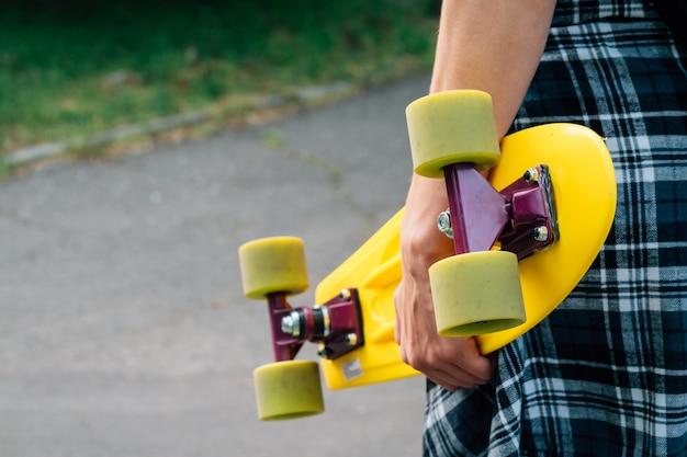 Meisje in jeans en een plaidoverhemd die een geel plastic skateboard met groene wielen houden