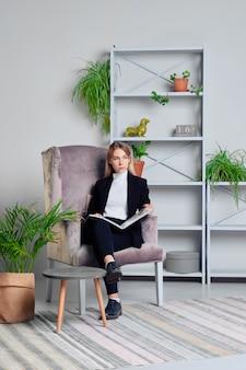 Meisje in jeans en jasjezitting in woonkamer met tijdschrift