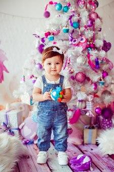 Meisje in jumpers staat met speelgoed voor de kerstboom